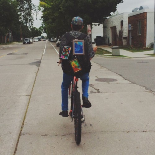 A man cycling with tie-dye art.