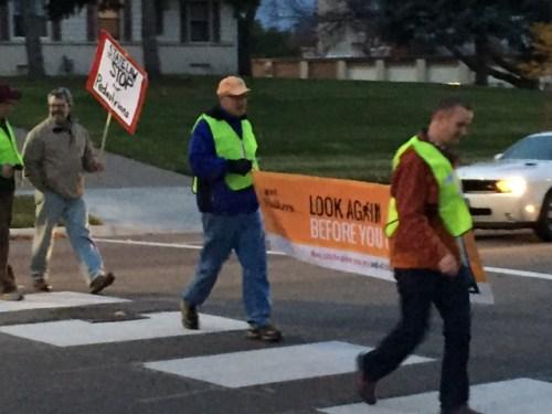 Sidewalk demonstration: Volunteers cross the street with signs