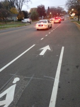A bike lane is shown in the foreground, as it ends the lines which define it are removed. The right line (towards the curb) is entirely gone, the left line (towards traffic) is maintained as a skip-striping pattern.