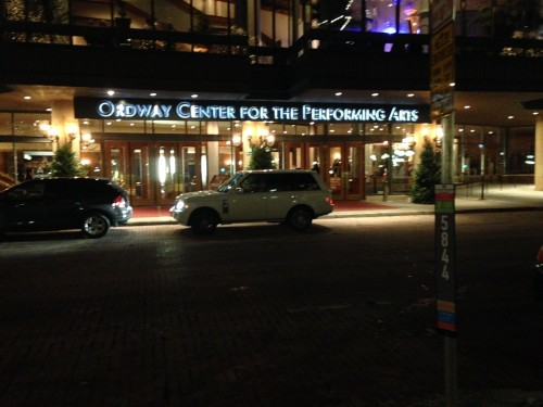 Two cars idle in front of the Ordway, across the street from an open parking stall.