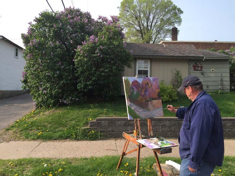 Don Holzschuh painting a lilac bush