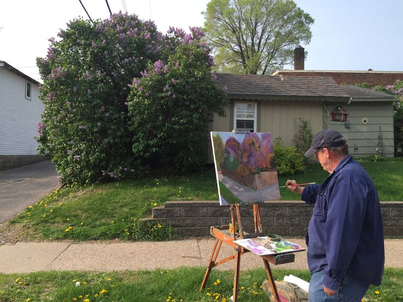 Don Holzschuh painting a lilac bush