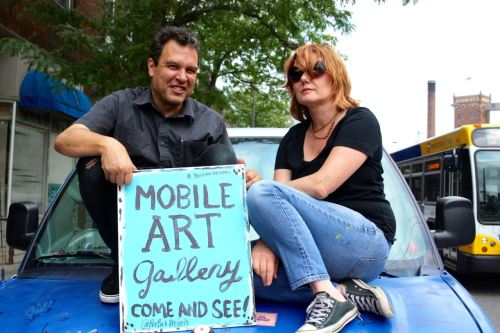 Chris Thompson (left) and Gretchen Seichrist (right) sit on their mobile art gallery van, which was parked on West 7th Street.