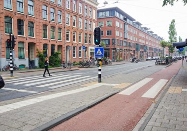 Even with a narrow single lane in each direction and slow motor vehicle speeds they've included a very well marked crossing as well as stop lights to insure that people can cross safely. On weekdays there is considerably more traffic.