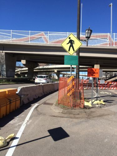 The camera faces a pedestrian detour beneath highway overpasses and on/off ramps. The area is narrow and delineated by jersey barriers on the left, separating the shared walk/bike path from the northbound traffic of Lyndale. To the right is a bright orange snow fence keeping people out of the construction area.