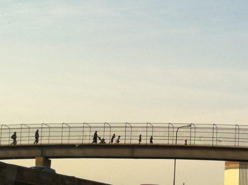 A number of people are crossing a pedestrian bridge over a highway, silhouetted against a diffusely clouded sky. All are heading to the right inside a chain link fence, full-silhouettes visible. There is a person pushing a stroller and a few children running ahead of them, with another adult many yards behind.