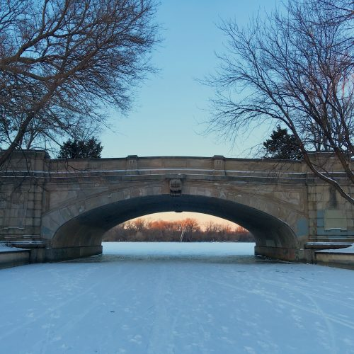 Standing on the frozen channel between Bde Maka Ska and Isles, looking north to the island through the bridge under Lake of the Isles Parkway. The sky over the island and the trees glow with sunset, but the sky visible above the bridge is an early twilight blue, with trees reaching inward on both sides.