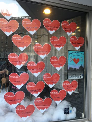 Window filled with red hearts that have reasons why people love the city