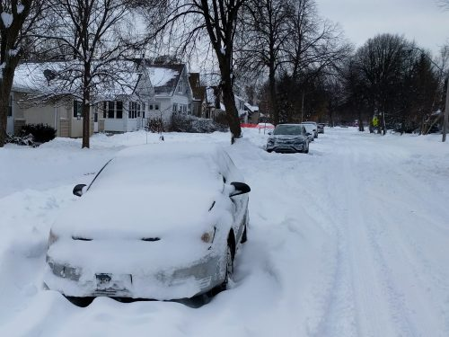 Snow-covered car on an unplowed street