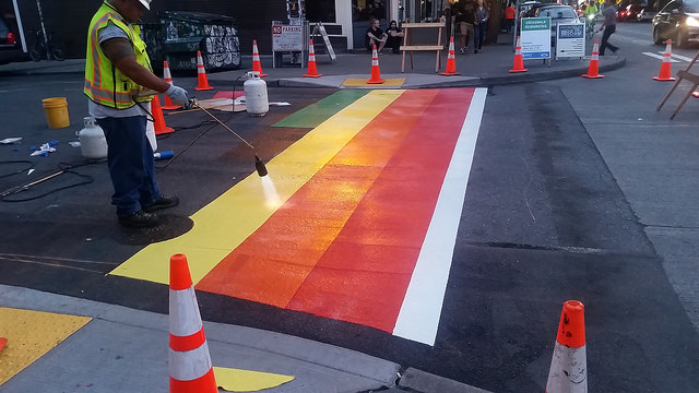 a city worker painting a durable rainbow crosswalk