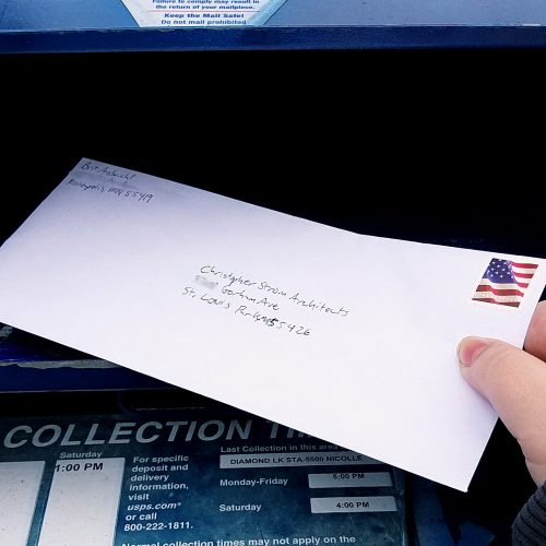 A white envelope about to enter a USPS collection box.