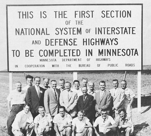 Minnesota Department of Highway employees posting by the sign.