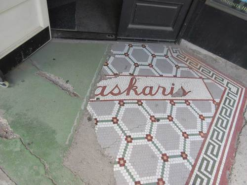 Remnant of gray, red and white octagonal pattern and the letters askaris in script in red on white background