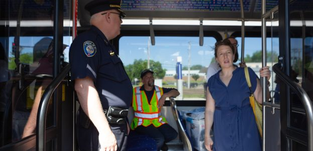 A woman onboard Metro Transit's Ceremonial First C Line bus looks in awe at the crowd as a Metro Transit police officer and a worker looks on. Rather than paying onboard, riders will pay before they board, and Metro Transit Police Officers will enforce payment.