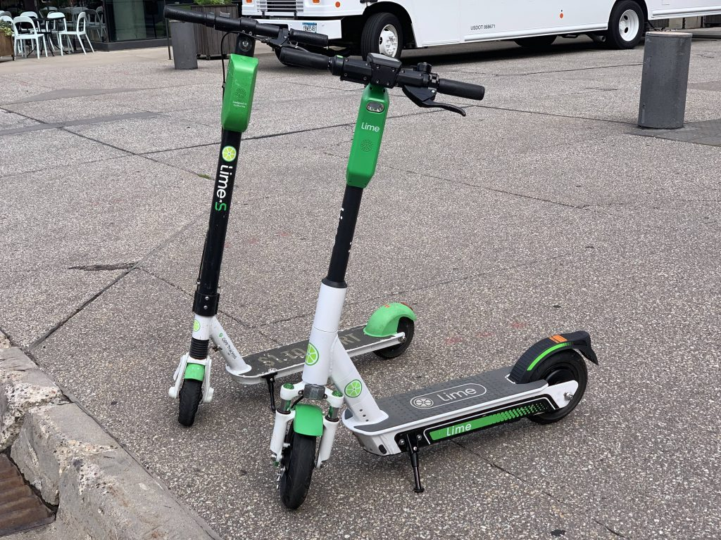 Lime Gen 3 Electric Scooter In Front Side By Side With Older Model