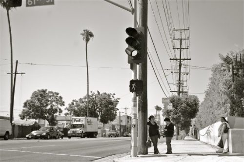 Photo of two people standing in the shade of a light pole