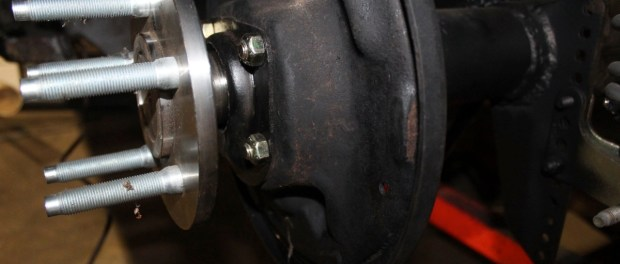"""Then the new axles were installed and the bolted on with some new grade-8 hardware. Yes, those studs are huge and may be a little bit of overkill, but that's OK. We used the small Ford bolt pattern, 5 on 4.5"""" for the rear, to match the front. All we have to do now is install the brakes."""