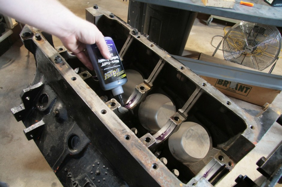With the pistons and rods assembled, we installed the new Sealed Power bearings (Z2320CP rod bearings, Z4924M main bearings) and coated them with some Royal Purple assembly lube. This is better than the paste prelube, but costs more too. We use it on everything. A set of ARP main studs were installed, then the crankshaft.