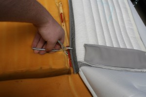 5.Then the top sections are ringed in place. There is a trick to this- first hook one side of the ring in the cover, then pop the lower hook under the bar and clamp. Make sure the cover is centered on the foam.