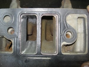"""7.The gasket is put on the head again to verify the porting. Each intake was widened by 0.100""""."""