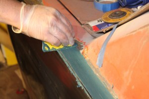 24.First, the welded areas were treated to a wiping of Duraglass. This fiberglass-reinforced body filler is not hydrophilic (water absorbing) like regular filler is. This makes it perfect for sealing any pinholes in the welds, protecting them from moisture.