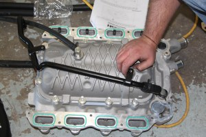 13. The intake includes an air-to-liquid intercooler. This takes up a lot of the room underneath the intake. The kit comes with some new piping to get all the right connections. Make sure the rubber hoses are routed correctly before mounting the intake. We learned that the hard way.