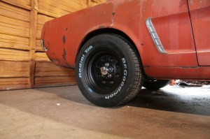 """02.This '65 Mustang has a set of vintage Cragar Street Lites installed. Wrapped in BF Goodrich Radial TA rubber, this is the perfect look and fit for an early Mustang. To make it stand out a little, the originally chromed wheels were powder coated black. These wheels require """"Mag-style"""" shank lug nuts. You can't use regular acorn lug nuts."""