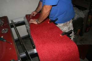 13.The new carpet comes in large square pieces, not cut to fit. Lay it on top of the original panel and trim it down carefully with a razor knife. Use some clamps on one side to keep it from shifting.