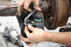 16. The new shock mounting plate gets bolted to the existing plate. To do this, the lower bolt (shock stud hole) is used and then a level placed on the mount to adjust the plate. Clamp the plate in place.