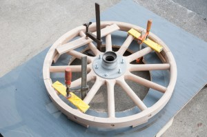 After the felloe is cut to size, the wooden wheel is clamped to a special table. This is to keep the wheel steady when it's time to install the steel rim onto the wooden felloe.