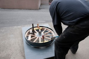The super heated rim is placed over the completed wooden wheel. It is then quenched with water, which causes the steel to contract and create a super strong bond between the wood and the steel.