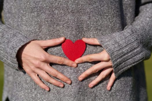 person holding heart shaped cut out