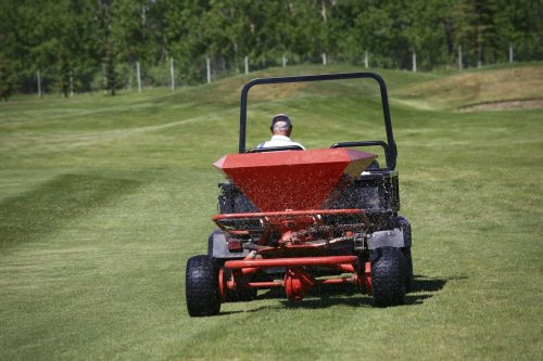 Applying fertiizer on a golf course. Fertilizer spreading machine on a golf course in summer. A maintenance employee at a golf course is applying nitrogen and other nutrients into the soil for enhanced growth. Themes include agronomy, turf, turf management, greens keeper, maintenance employee, fertilizer, growing, cutting, lawn, turf grass maintenance, applications, and fungicide.
