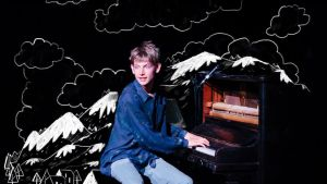 A man sits at an upright piano in front of a drawn world of mountains and clouds.