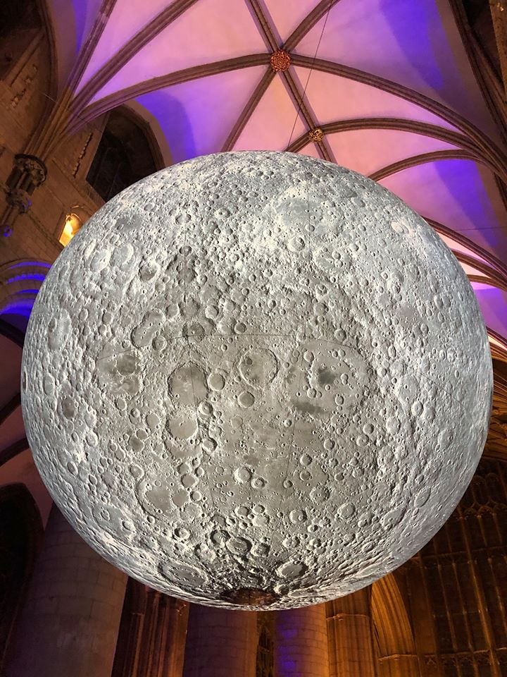 In the knave of a cathedral is a replica of the Earth's moon. It is suspended on wired.