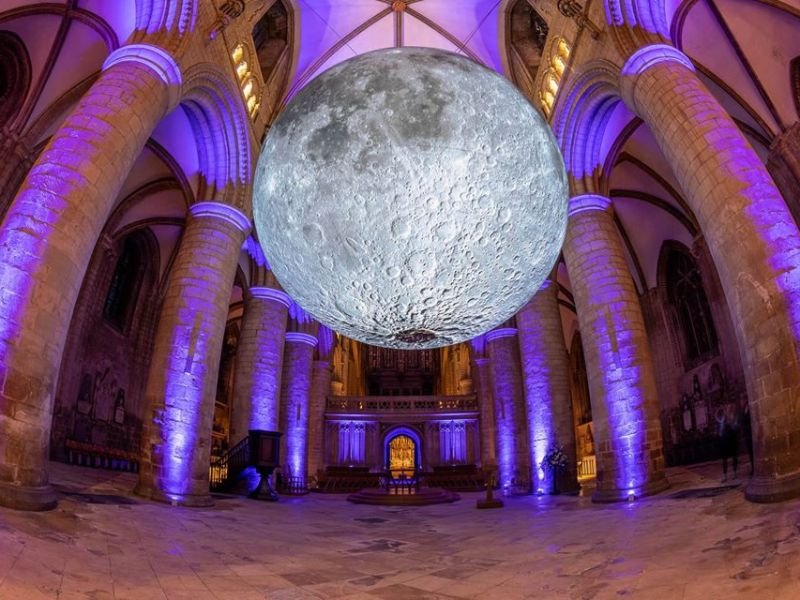 A model/replica of the moon is suspended in the knave of a cathedral.