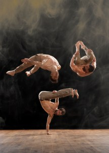 In a dark studio two people do arial dance moves. A third is doing a handstand.