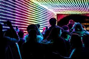 People move through a tunnel of multi coloured lights.