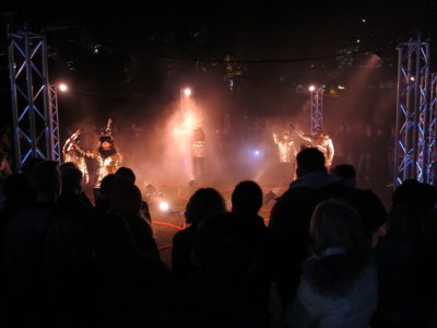 An outdoor performance at night. People walk around in silver jackets and virtual reality headsets while light pours down on them from above.