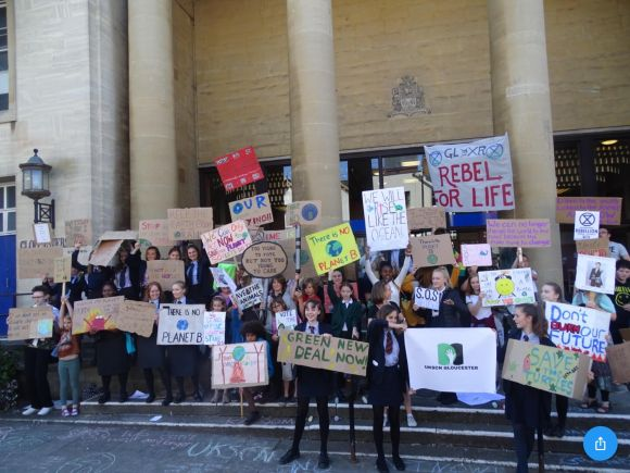 Students hold signs protesting climate change inaction.