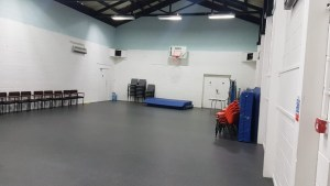 A community sports hall. The room has chairs pushed the the sides of the room and is largely empty.
