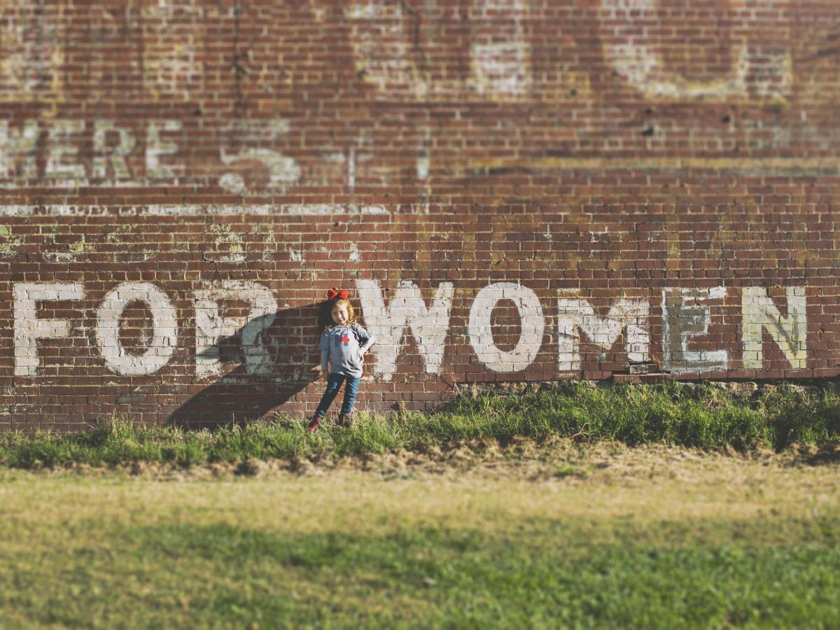 "A young girl stands in a field in front of a large red brick wall which has the text ""FOR WOMEN"" painted onto it."