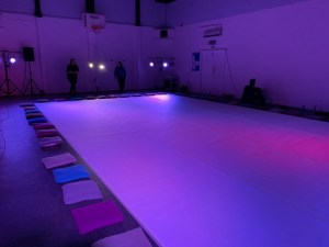 A community sports hall with a large roll of paper filling up around two thirds of the room. Cushions surround the paper. At the end of the hall are a series of theatrical lights and speakers. The lights give a purple glow over the room. Two people stand casually at the end of the room.