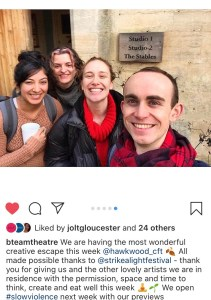 "An Instagram screenshot. The image is of four smiling people in front of a sign that reads ""Studio 1 Studio 2 The Stables"". Beneath the text reads ""We are having the most wonderful creative escape this week. All made possible thanks to @strikealightfestival - thank you for giving us and the other lovely artists we are in residence with the permission, space and time to think, create and eat well this week. We open #slowviolence next week with our previews"""