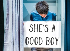 "A person stands in a dressing cubicle holding a sign that reads ""SHE'S A GOOD BOY"""