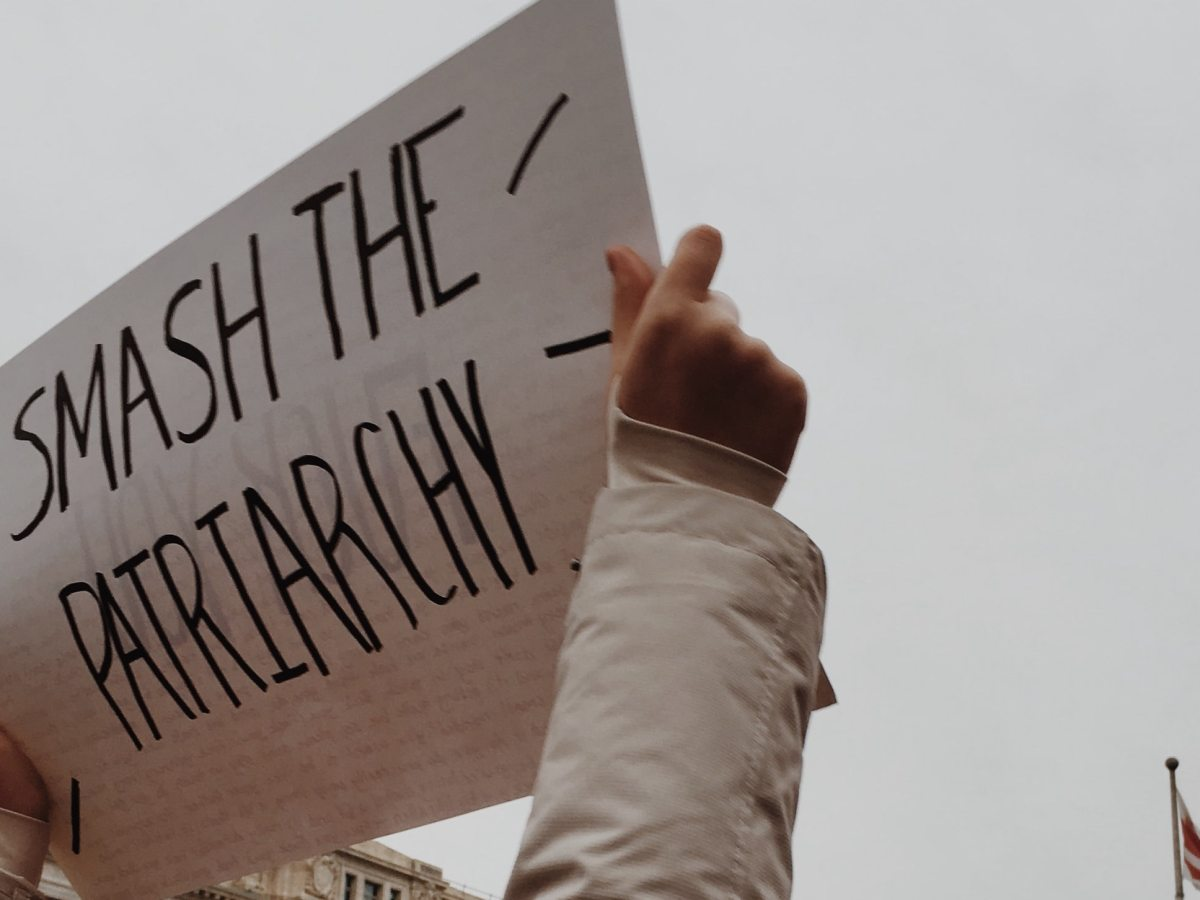 "Sign reading ""Smash the patriarchy"" is held up in front of a grey sky by two hands"