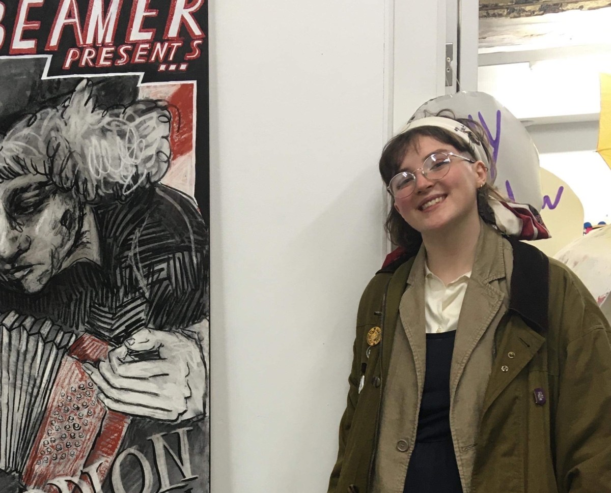 Artist Hannah Whyte leant against a white wall next to a piece of half hidden artwork. Hannah is wearing a green army style jacket and glasses.