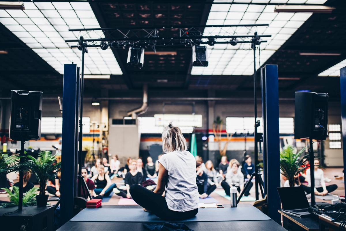 A person on a yoga mat on a stage in front of a class full of people.