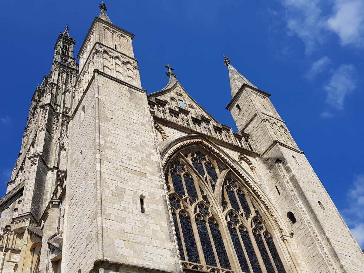 Looking up at Gloucester Cathedral from the ground showcasing its impressive size and windows.