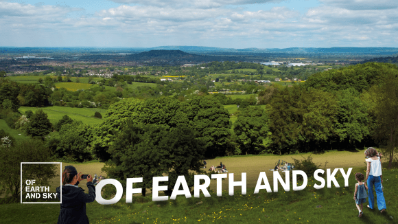 Large white letters saying Of Earth and Sky in a field with views over Gloucestershire.